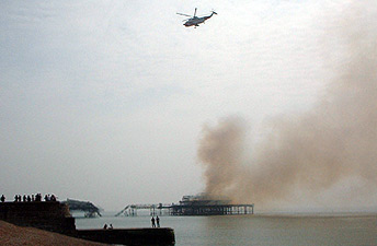 Smoldering West Pier and helicopter